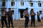 Police stand in front of a mosque and school dormitory that were damaged in a fire in Yangon (Photo: Reuters)