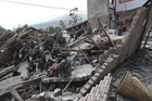 Rescue workers sit atop rubble after the earthquake (Reuters)