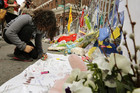 A young girl writes a message on a sign at a memorial to the victims near the scene of the Boston Marathon bombings (Reuters)