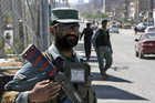 Afghan security officials stand guard following militant attacks at a provincial court and a bank building (AAP)