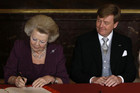 Queen Beatrix of the Netherlands signs an act of abdication next to her son Willem-Alexander (Reuters)