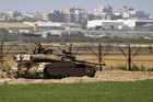 An Israeli soldier sits atop a tank just outside the northern Gaza Strip (Reuters)