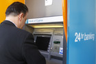 A man transfers money using a Bank of Cyprus ATM (Reuters)