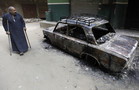 Cairo, EgyptA man walks in front of a burnt car and a house belonging to a Christian after clashes between Muslims and Christians  (Reuters)