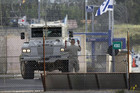 A United Nations peacekeeper directs an armoured vehicle in the Golan Heights (Reuters)