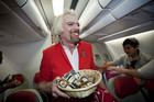 Sir Richard Branson, dressed in drag as a flight attendant, greets passengers aboard an Air Asia flight (AAP)