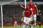 Lukas Podolski, left, celebrates his first goal of two for Arsenal against Wigan at Emirates Stdaium (Reuters)