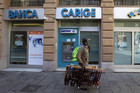 A street vendor walks in front of Carige bank in Genoa, Italy (Reuters)