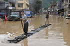 A journalist (R) records a video on a raft as a man paddles along flooded street after heavy downpours hit Jianghua Yao Autonomous County, Hunan province (Reuters)