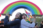 Two young women pose underneath a plastic rainbow (AAP)