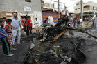 Residents gather at the site of a car bomb attack in the Kamaliya district in Baghdad (Reuters)