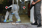 An Israeli police forensics expert investigates the bank after the shooting (Reuters)