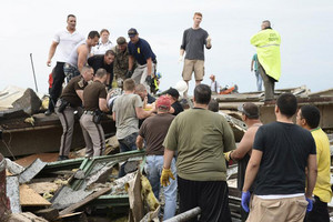 Rescue workers help free one of the 15 people that were trapped in the Moore hospital complex (Reuters)