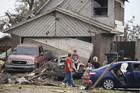 People are seen next to a damaged house in Moore, Oklahoma (Reuters)