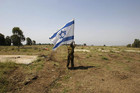 An Israeli soldier places a flag close to the ceasefire line between Israel and Syria at Golan Heights (Reuters)