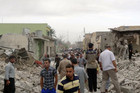 Residents stand amid rubble at blast scene in Tuz Khormatu town, northern Iraq (Reuters)