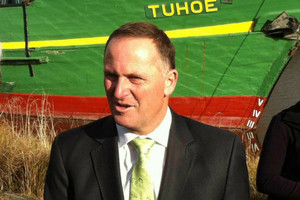 John Key talks to reporters, coincidently in front of a boat named 'Tuhoe' (photo: Hamish Clark/3 News)
