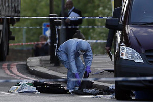 Forensics officers examine the scene where one man was killed (Reuters)