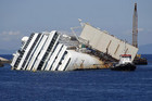 The capsized cruise liner Costa Concordia still lies outside Giglio harbour (Reuters)