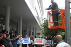 Mr Dixon-McIvor launches his protest from a cherry-picker