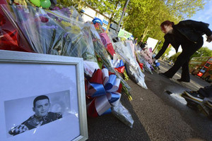 A picture of victim Drummer Lee Rigby alongside flowers left near the scene of his killing (Reuters)