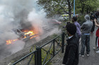 Bystanders take photos of a row of burning cars in the suburb of Rinkeby after youths rioted in several different suburbs around Stockholm (Photo: Reuters)