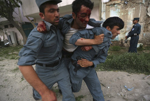 A wounded Afghan policeman is being carried away from the site of an explosion in Kabul  (Reuters)