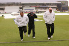 Umpires Steve Davis (right), Marais Erasmus (left) and NZ coach Mike Hasson run off in the rain (Photosport)