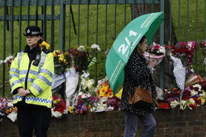 A policewoman stands near floral tributes for Drummer Lee Rigby (Reuters)