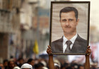 A Shi'ite anti-government protester holds up a poster of Syrian President Bashar al-Assad during a demonstration (Reuters)