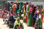 Somali women and their babies queue for relief food south of Mogadishu (Reuters file)