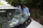 Security officials inspect the damaged car, which prosecutor Chaudhry Zulfikar was travelling in when he was attacked (Reuters)