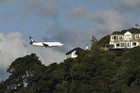 An Air New Zealand plane flies over houses in Mount Victoria (Reuters)