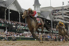 Orb, ridden by jockey Joel Rosario, passes the famous twin spires and crosses the finish first (Reuters)
