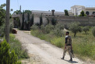 A Free Syrian Army fighter walks in the Khan al-Assal area, near Aleppo (Reuters)