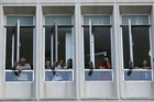 Employees stand at the windows of the Greek state television headquarters (Reuters)