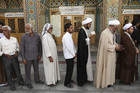 Iranian men wait in line to vote at a polling booth in Qom, 120km south of Tehran (Reuters)