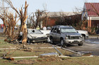 People walk near cars and trees damaged by a tornado in Oklahoma (Reuters)