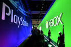 Attendees walk between the PlayStation and Xbox exhibits at the E3 (AAP)