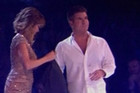 Simon Cowell cleans himself off after being hit with eggs