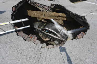Pamela Knox waits for rescue after a massive sinkhole opened up underneath her car in Toledo, Ohio (Reuters)