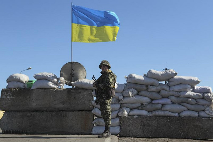 A Ukrainian soldier stands guard at a checkpoint near a town that is adjacent to Crimea (Reuters)