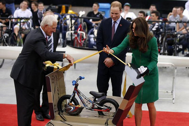 Britain's Prince William and his wife Catherine, Duchess of Cambridge, are presented with a bicycle for Prince George (Reuters)
