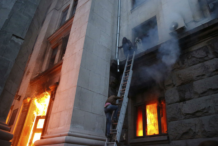 People wait to be rescued on the second storey's ledge during a fire at the trade union building in Odessa (Reuters)