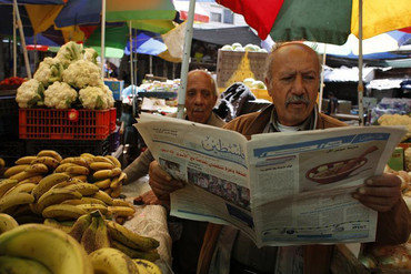 A Palestinian man selling fruits and vegetables reads a copy of a pro-Hamas newspaper (Reuters)