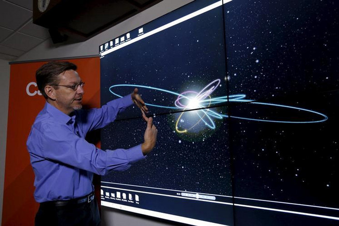 Professor of Planetary Astronomy Mike Brown speaks in front of a computer simulation of the probable orbit of Planet Nine (Reuters)